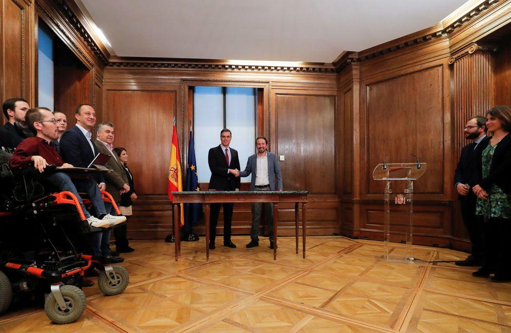 Foto: Pedro Sánchez y Pablo Iglesias rubrican su pacto para un Gobierno de coalición este 30 de diciembre en el Congreso, con sus equipos. (Reuters)