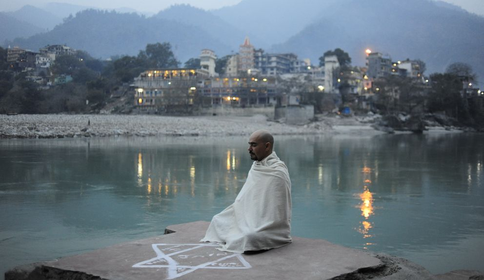 Foto: Alfredo Rey meditando con su ashram detrás en la ciudad de Risikesh. (Alfredo Rey)