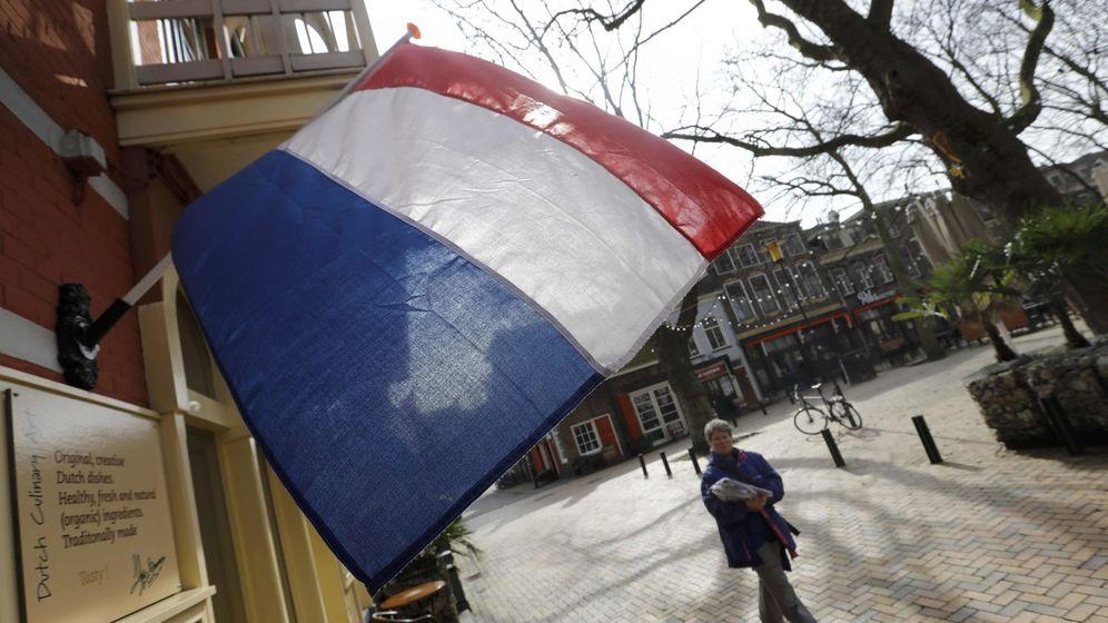Foto: Una mujer pasa por debajo de una bandera holandesa el día antes de las elecciones en Delft, el 14 de marzo de 2017. (Reuters)