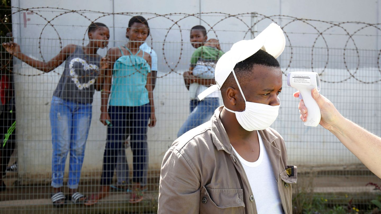 Controles de temperatura a un hombre protegido con una mascarilla, en Sudáfrica. (Reuters)