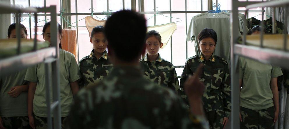 Foto: Un instructor que perteneció al Ejército chino habla con estudiantes del Qide Education Center, ubicado en Pekín, en su dormitorio (Reuters).