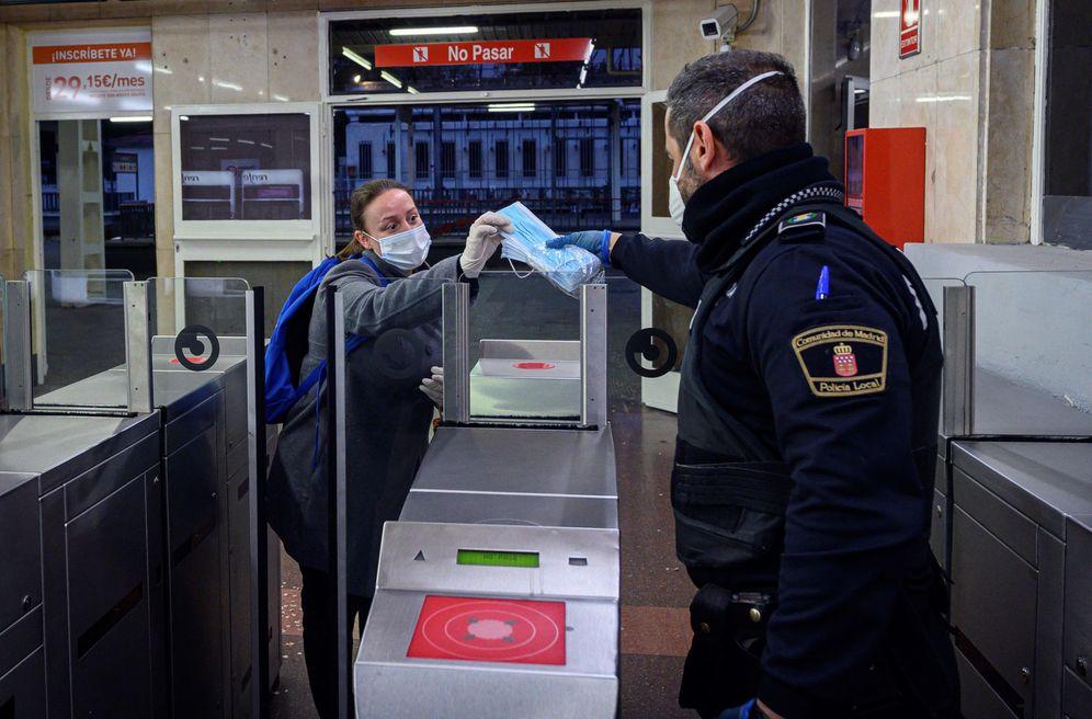 Foto: Policías entregan mascarillas en la estación de Cercanías de Alcalá de Henares, en Madrid, este 13 de abril. (EFE)