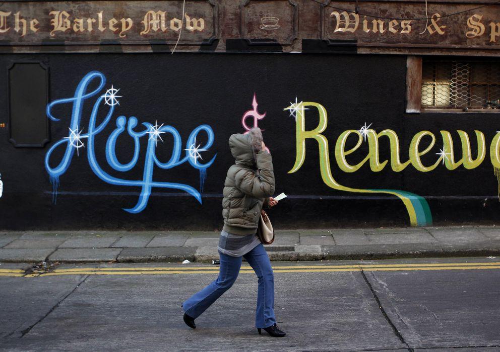 """Foto: Una mujer pasa ante una pintada en Dublín que reza: """"Esta ciudad necesita esperanza y renovación"""" (Reuters)."""