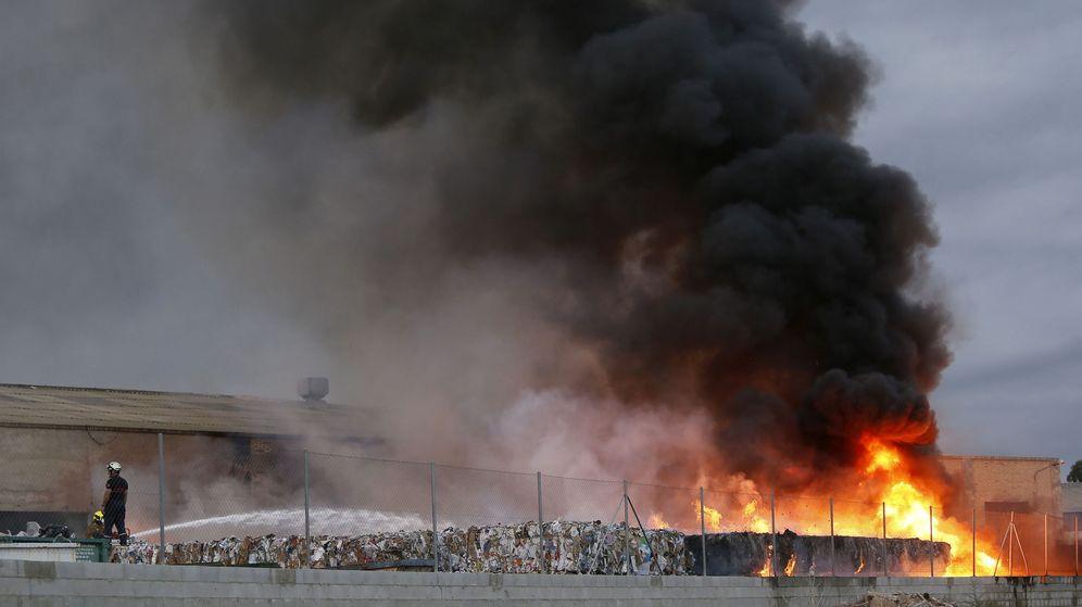 Foto: Los bomberos intentan sofocar las llamas de un aparatoso incendio en una planta de reciclaje de Alicante (Manuel Lorenzo / EFE)