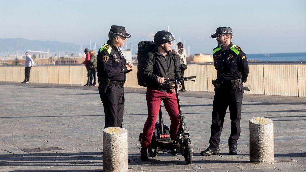 Foto: Agentes de la Guardia Urbana de Barcelona informan a un ciudadano, que circula con un patinete eléctrico, sobre la normativa de circulación que afecta a este tipo de patinetes. (EFE)