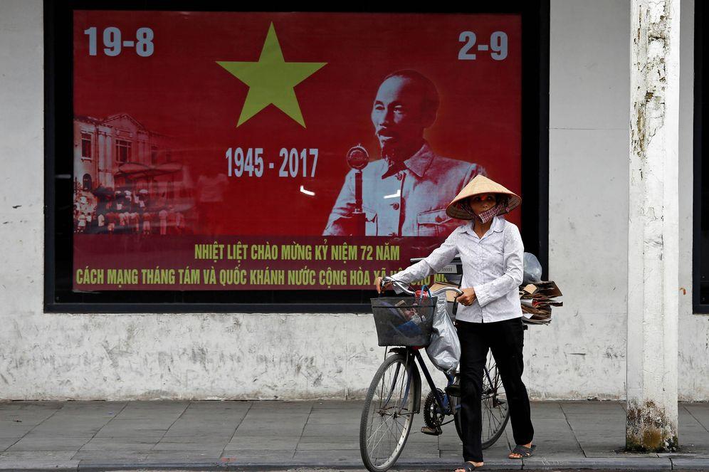 Foto: Una mujer pasa por delante de un poster de Ho Chi Minh en Hanoi, el 30 de agosto de 2017. (Reuters)
