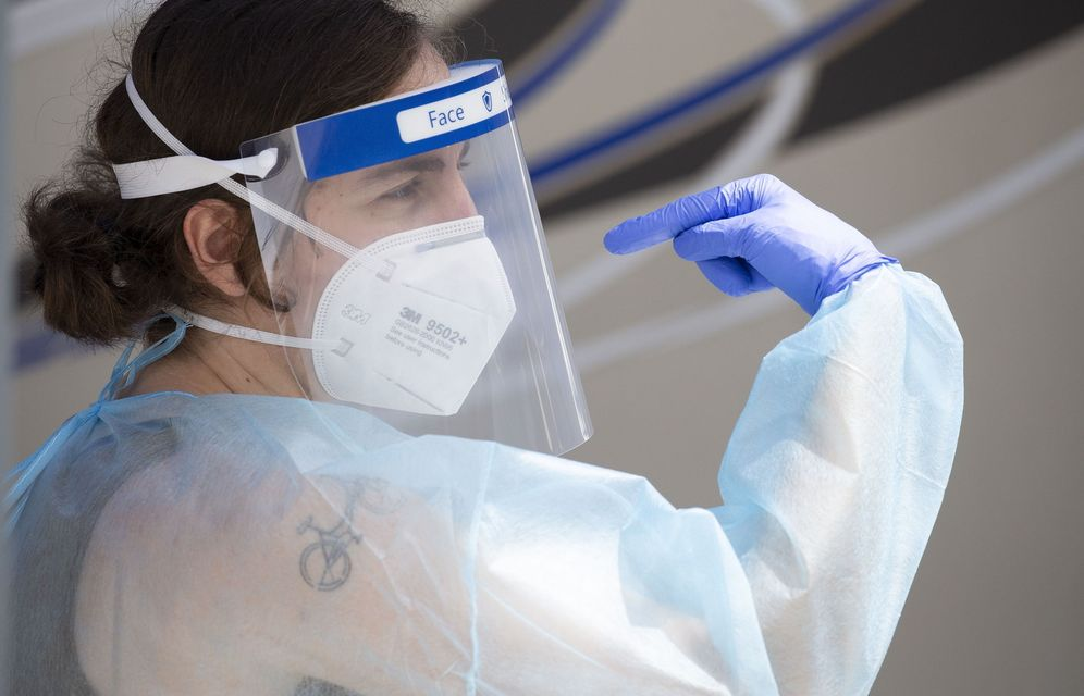 Foto: Una enfermera explica a un paciente cómo colocarse la máscara. (Reuters)