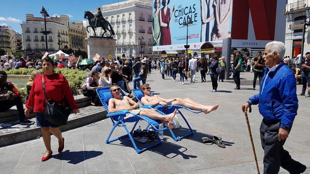 Foto: Dos turistas toman el sol semidesnudos en la Puerta del Sol de Madrid. (Henar Ortega)