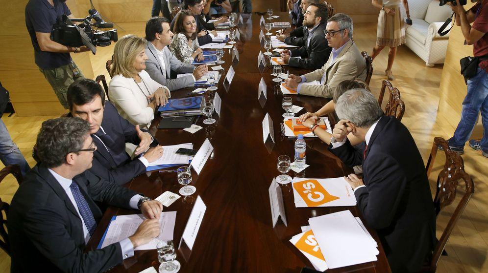 Foto: Los equipos negociadores de PP y Ciudadanos, durante la quinta jornada de trabajo para buscar un pacto de investidura. (EFE)