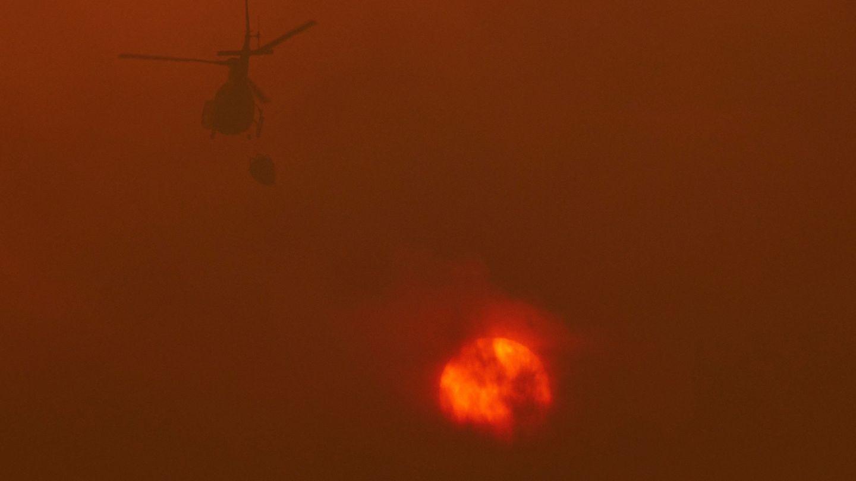 Un helicóptero de los servicios de extinción trabaja junto a las llamas. (EFE)