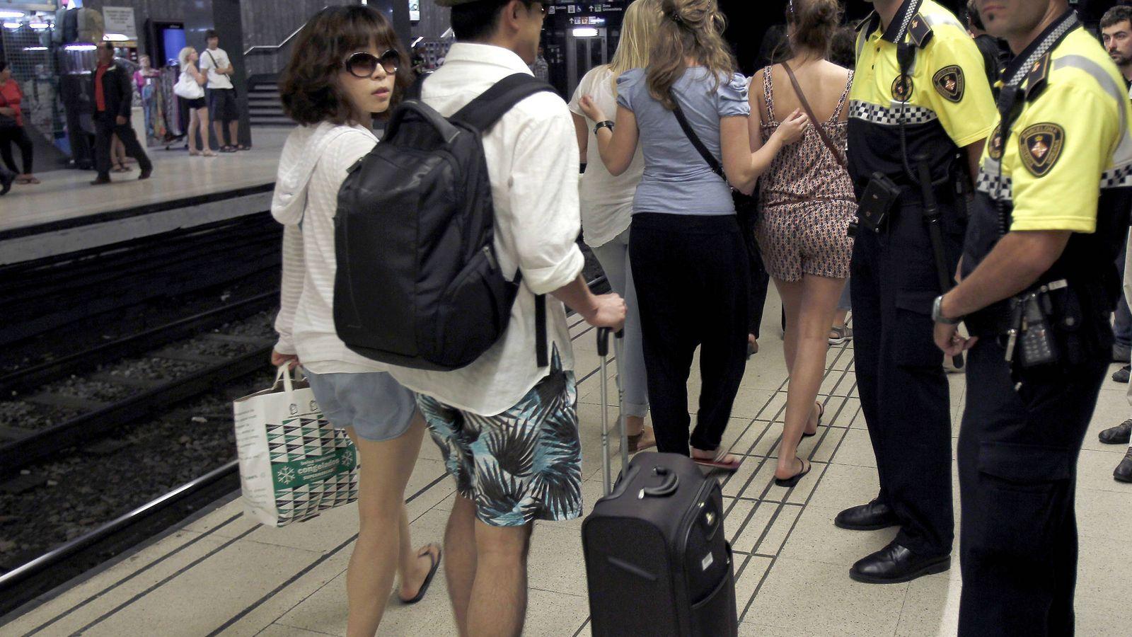 Foto: Dos agentes de la Guardia Urbana informan a los turistas de la presencia de carteristas en el metro de Barcelona, en una foto de archivo. (EFE)