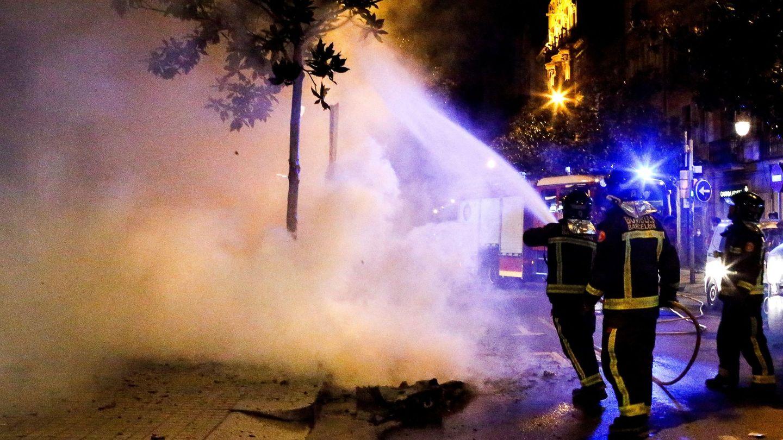 Los bomberos apagan un contenedor que arde en el barrio de Grácia. (EFE)