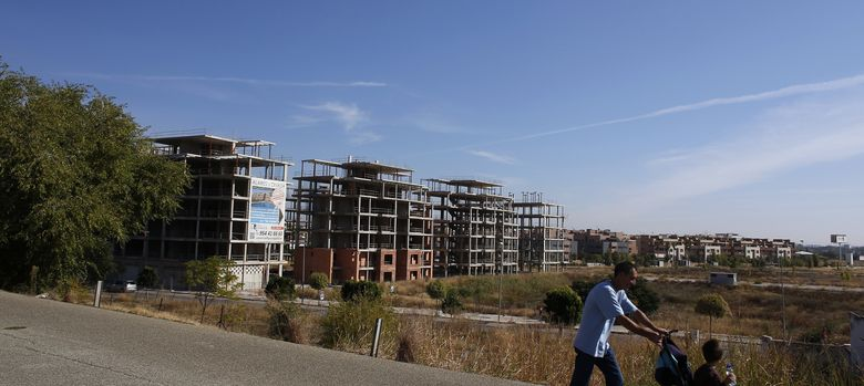 Foto: Un hombre camina ante unos edificios en construcción cerca de Sevilla (Reuters).