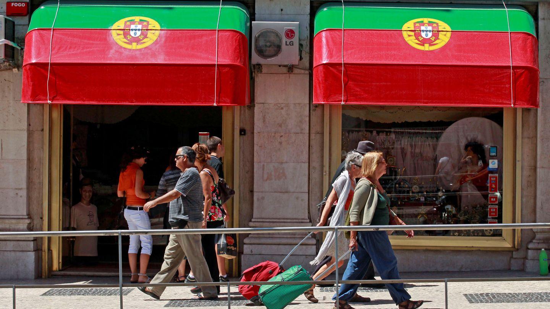 Turistas y residentes pasan por delante de una tienda en el centro de Lisboa. (Reuters)
