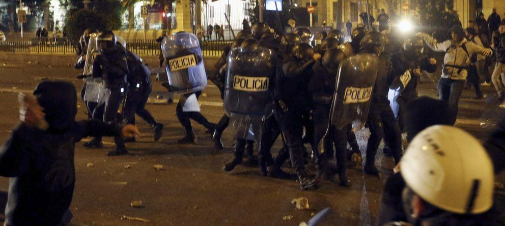 Foto: Policías antidisturbios se protegen en las inmediaciones de la Plaza de Cibeles el 22-M. (EFE)