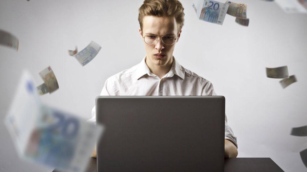 Foto: Un joven trabaja desde su portátil mientras vuelan billetes. (iStock)