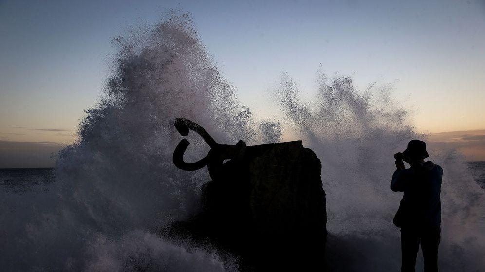 Foto: Una persona fotografía una ola al romper en el Peine del Viento. (EFE)