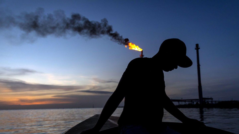 Un pescador en una lancha para la pesca nocturna de camarones, mientras pasa por un quemador de combustible llamado 'Mechurrio' en Venezuela. (EFE)