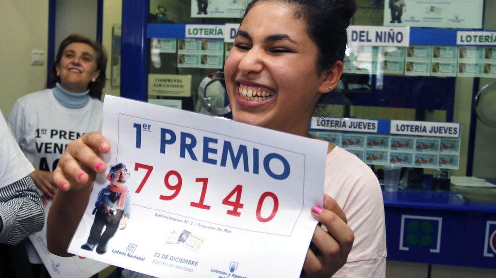 Foto: Una joven sonríe con una copia del primer premio de la Lotería de Navidad vendido en Roquetas de Mar (EFE)