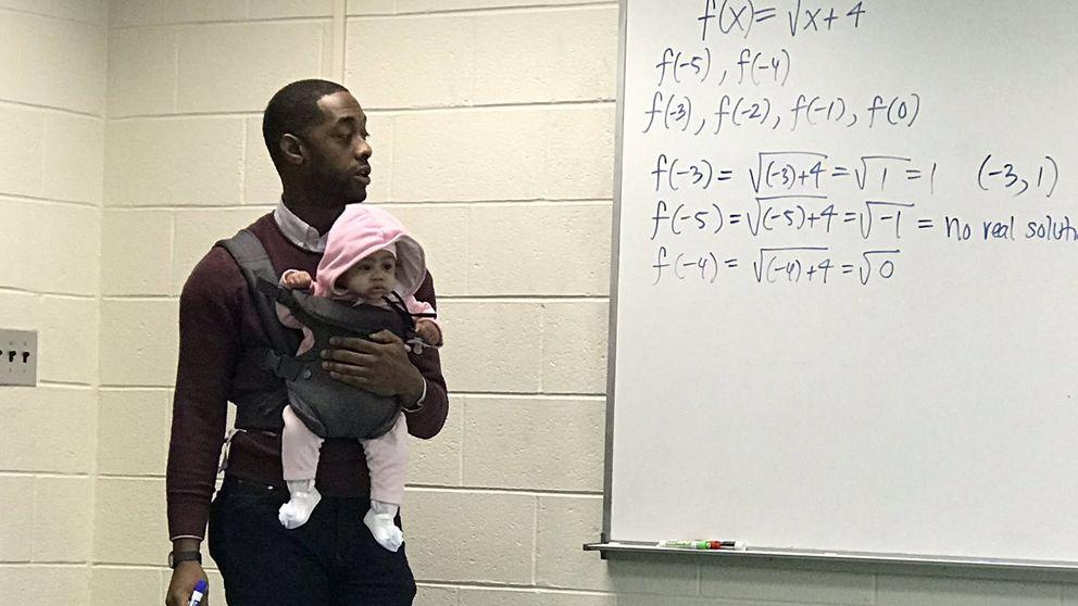 Un profesor da clase sosteniendo al bebé de un alumno para que pudiera atender