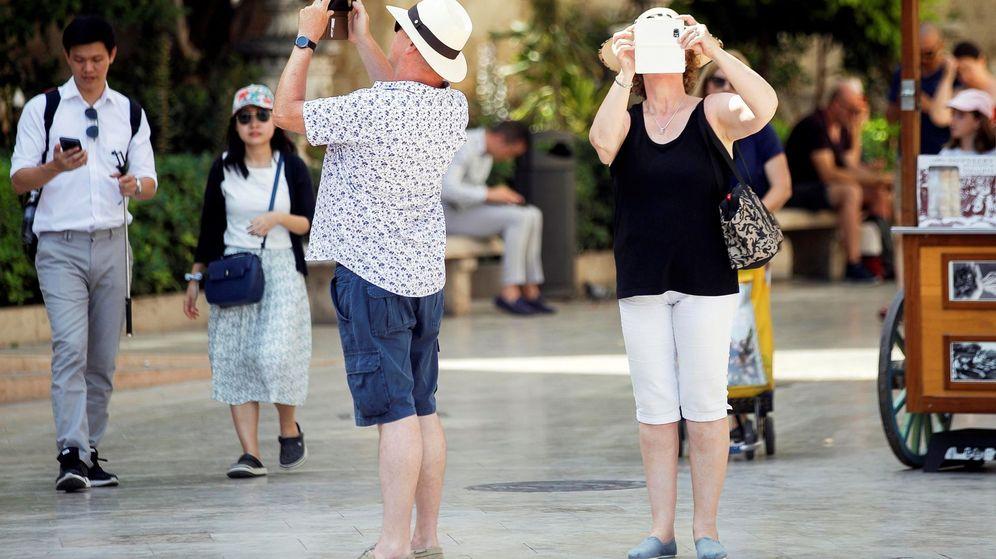 Foto: Dos turistas consultan su teléfono móvil en la Comunidad Valenciana. (EFE)