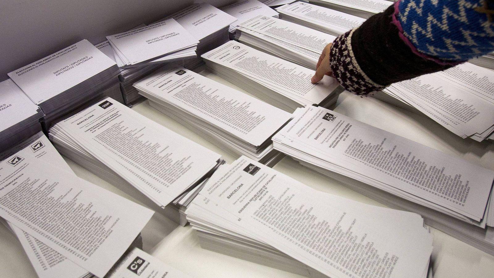 Foto: Una vecina de Barcelona escoge una papeleta en un colegio electoral. (EFE)