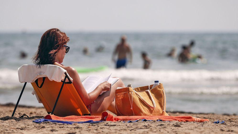 Foto: Una mujer lee en la playa de la Patacona de Alboraya. (EFE)