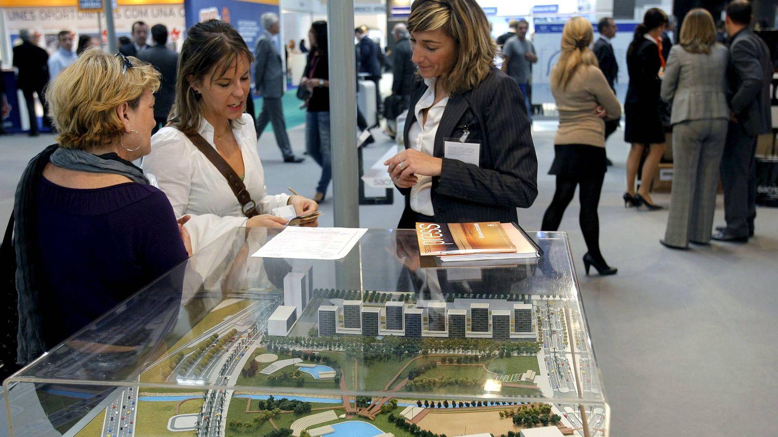 Foto: Varias personas observan la maqueta de una urbanización en un salón inmobiliario (España). (EFE)