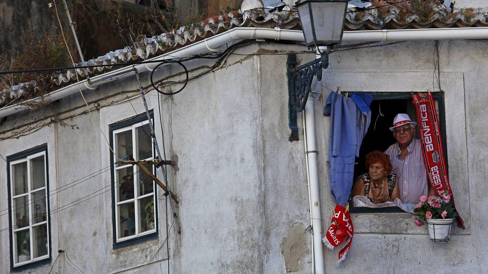 Foto: Unos ancianos en una ventana en Lisboa. (Reuters)