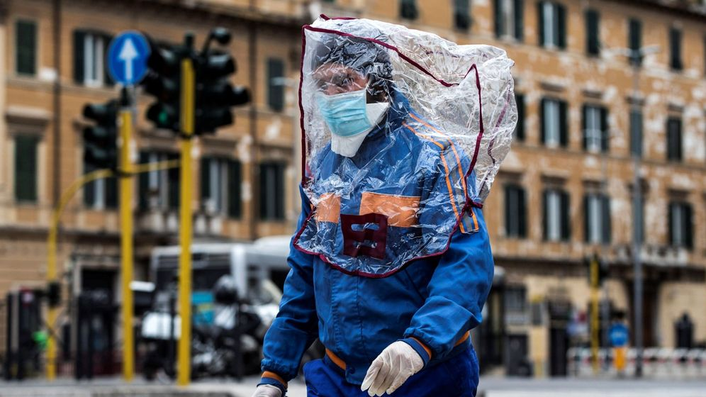 Foto: Un hombre con una bolsa de plástico en la cabeza camina por una calle de Roma. (EFE)