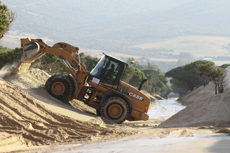 Una excavadora retira arena de la duna de Valdevaqueros. (EFE)