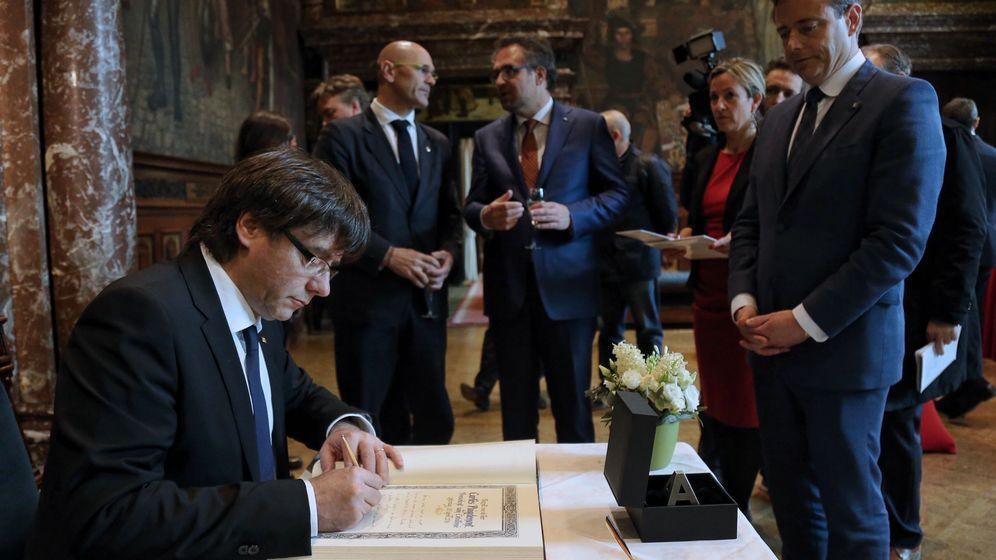 Foto: El presidente de la Generalitat, Carles Puigdemont (i), durante la firma del libro de oro del Ayuntamiento de Amberes. (EFE)