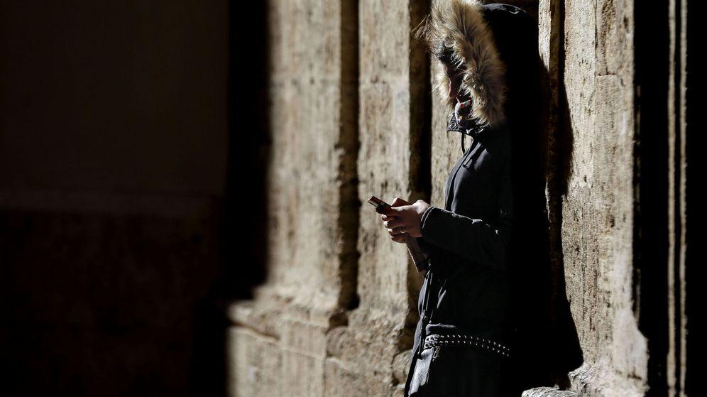 Foto: Una joven consulta su móvil en Valencia. (EFE)