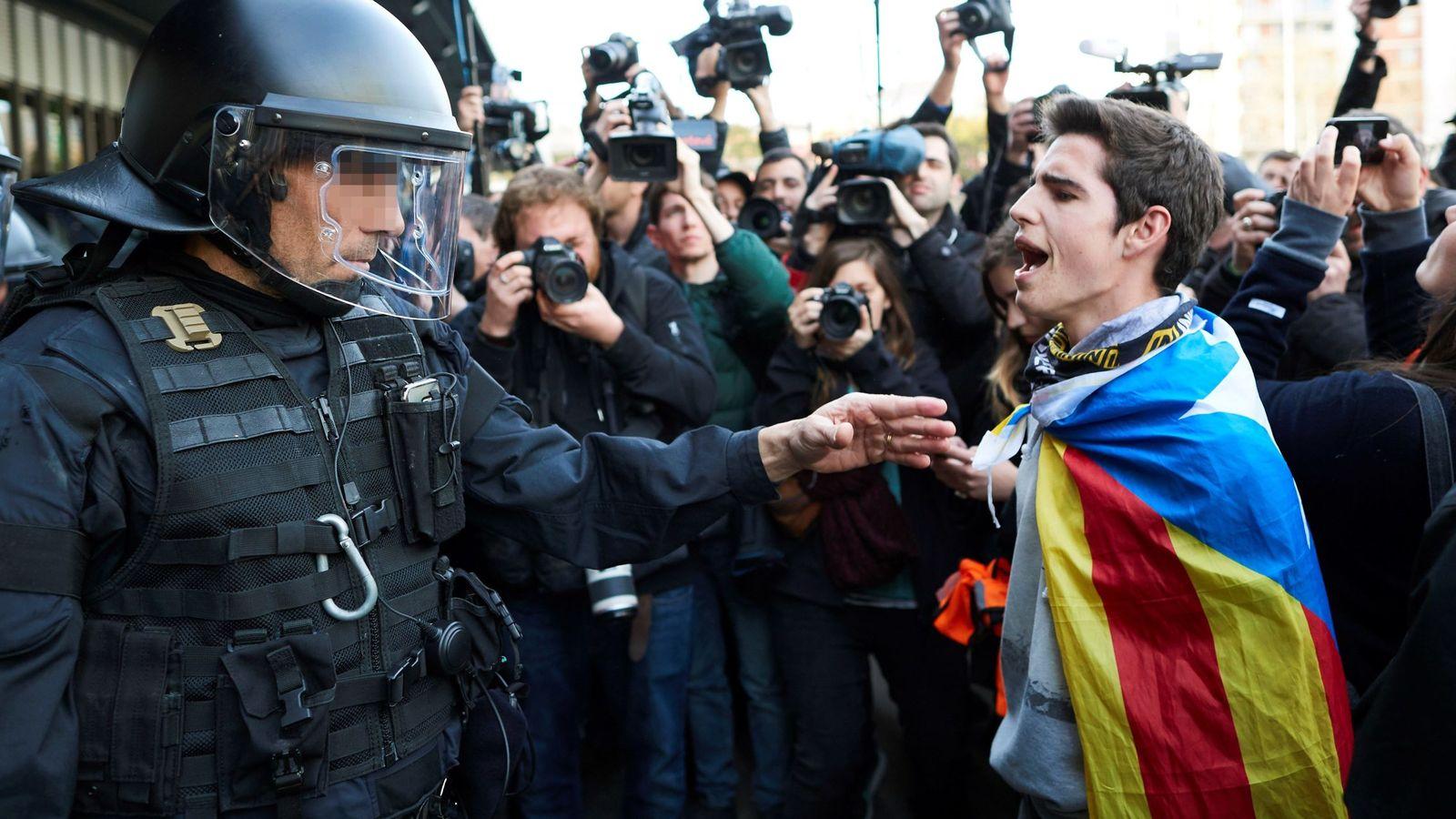 Foto: Un joven, ante un 'mosso' en la concentración que miembros de los CDR llevaron a cabo frente a la estación de Sants de Barcelona. (EFE)