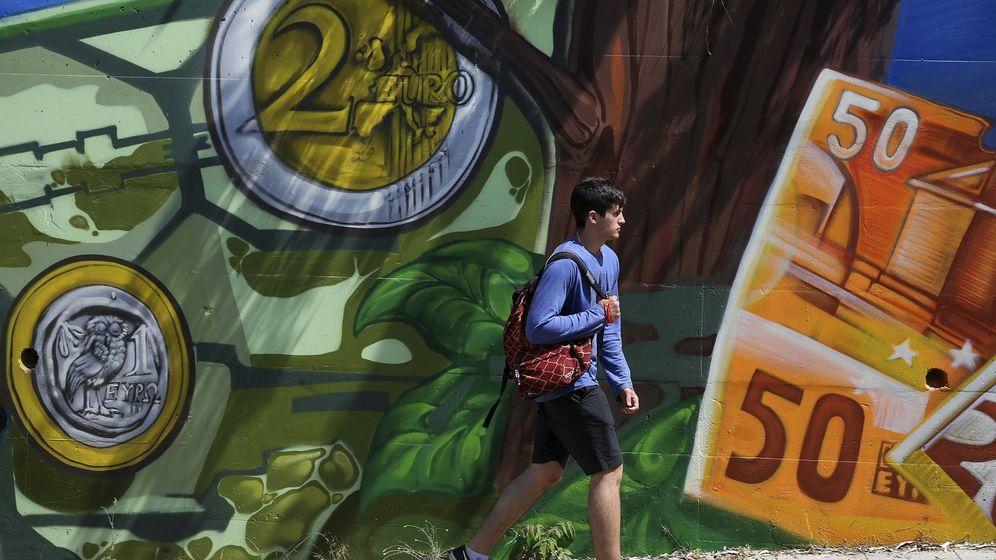 Foto: Un joven pasa junto a una pintada de billetes y monedas de euro. (EFE)
