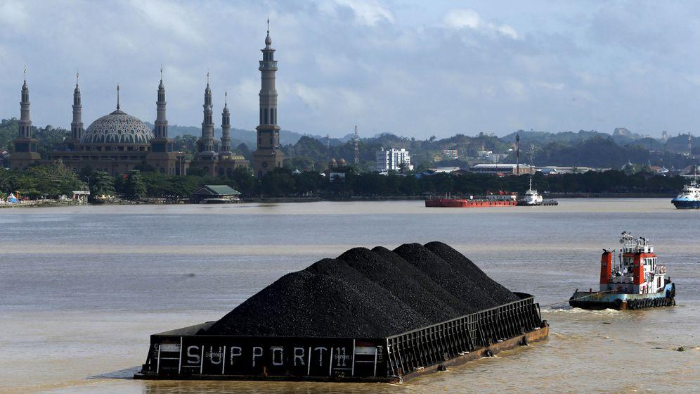 Foto: Un barco tira de una plataforma con carbón a lo largo del río Mahakam, en Indonesia (Reuters)