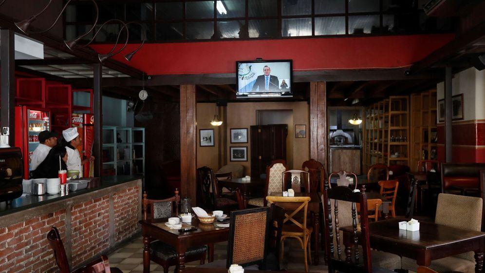 Foto: Empleados de un restaurante en el centro de Ciudad de Guatemala mientras observan un mensaje del presidente de Guatemala, Alejandro Giammattei (EFE)