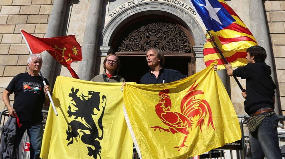 Foto:  Cuatro personas sostienen las banderas (de izda a dcha) de las regiones de Occitania, Flandes, Valonia y la estelada, ante el Palau. (EFE)
