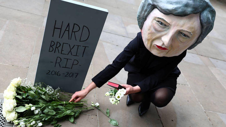 Un manifestante con una máscara de Theresa May posa fuera de Downing Street. (Reuters)