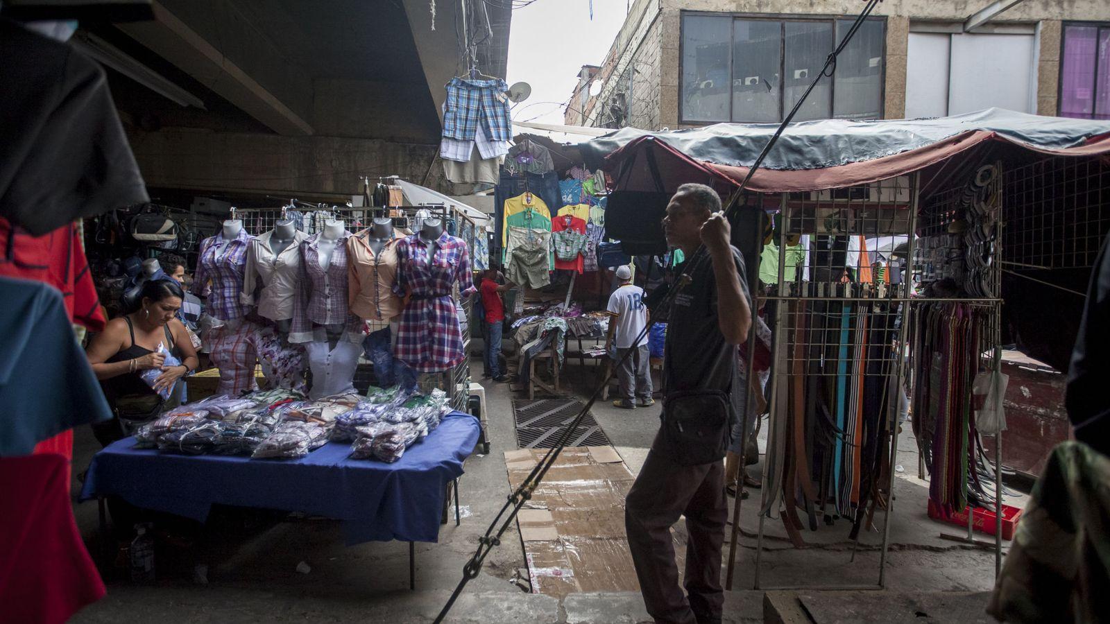 Foto: Un vendedor espera la llegada de los primeros clientes a un mercado popular en Caracas. (EFE)