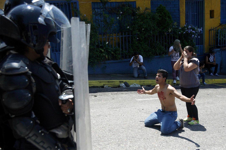 Foto: Un joven con sangre en su pecho se arrodilla ante la policía tras la muerte de Kluiver Roa en una protesta en San Cristóbal (Reuters).