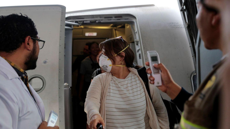 Pasajeros, examinados al salir de un avión. (EFE)
