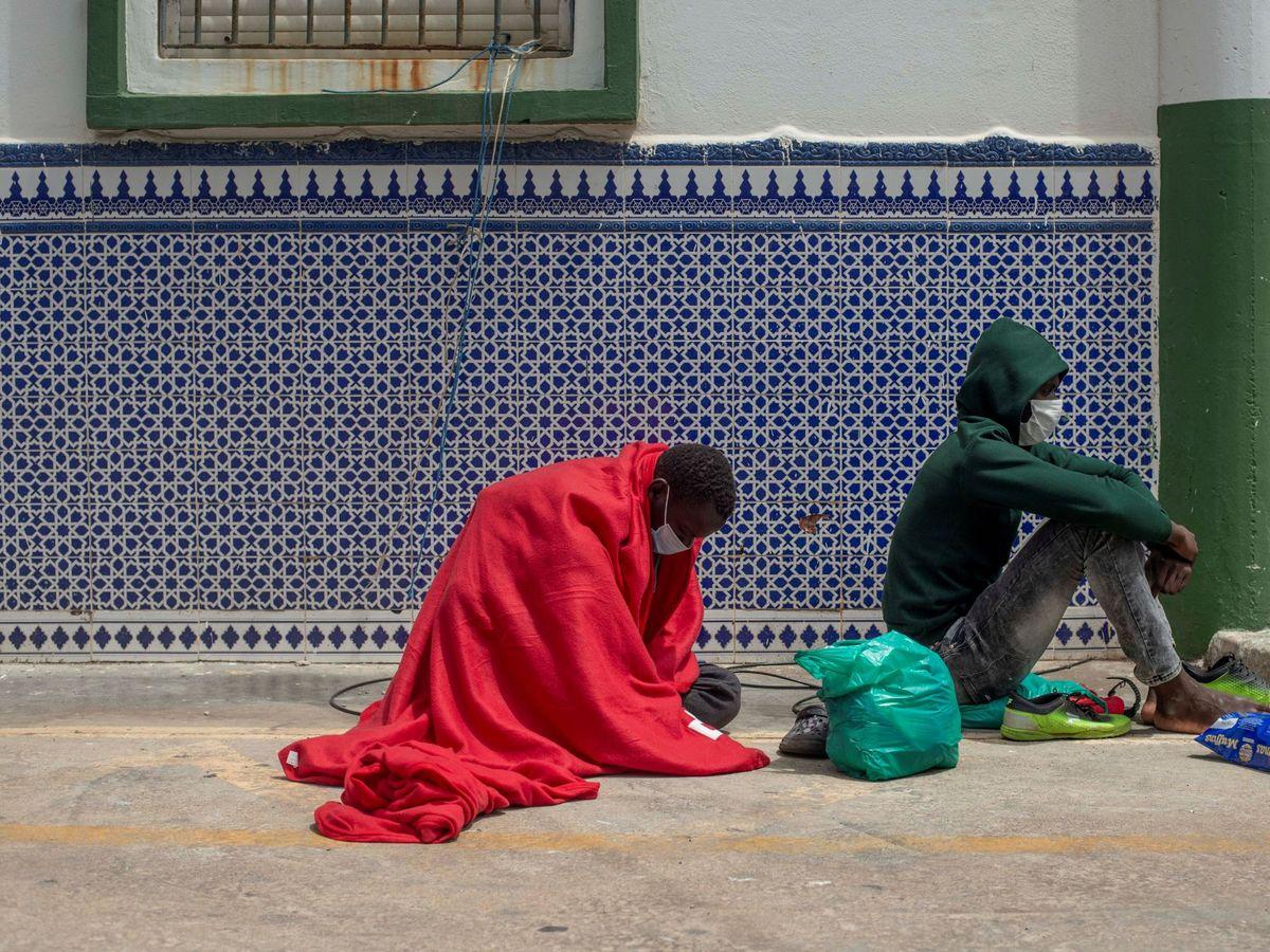 Foto: Dos migrantes que buscan asilo esperan este viernes a ser ayudados a las puertas del polígono industrial cercano a la playa de El Tarajal, en Ceuta. (EFE)