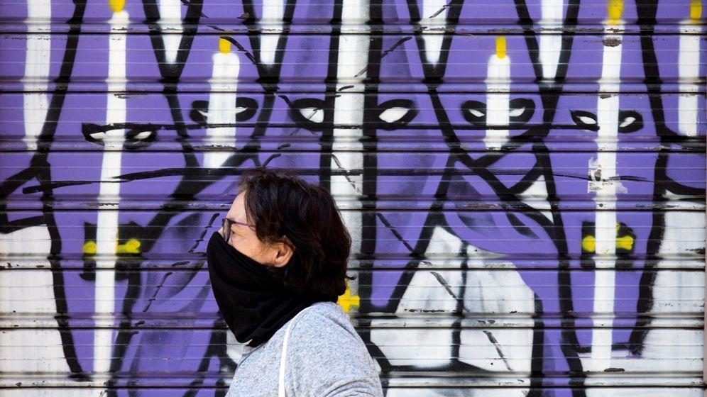 Foto: Una mujer camina delante de un mural sobre la Semana Santa e Málaga (EFE)