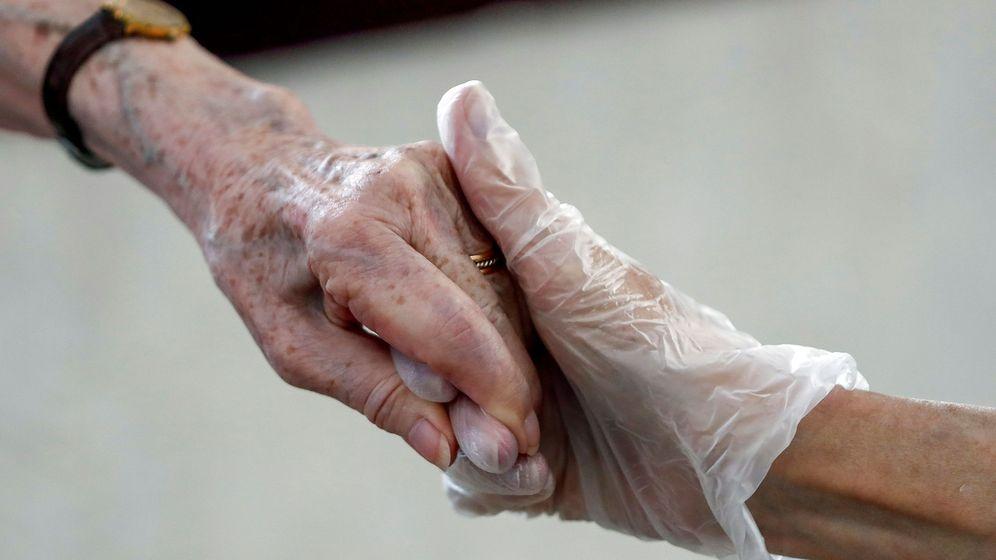 Foto: Una hija saluda a su madre, interna en una madre en una residencia de ancianos de Madrid. (EFE)