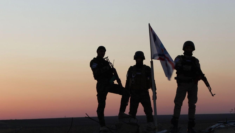 Foto: Miembros de la milicia asiria NPF posan junto a su bandera para la prensa en Telskoff. (Foto: Ferran Barber)