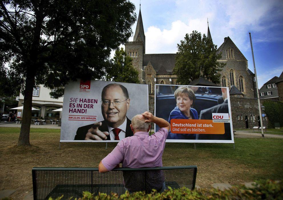 Foto: Un hombre observa los carteles electorales de Ángela Merkel (d), de la CDU, y del candidato de la oposición Peer Streinbrück (i), del Partido Socialdemócrata, e