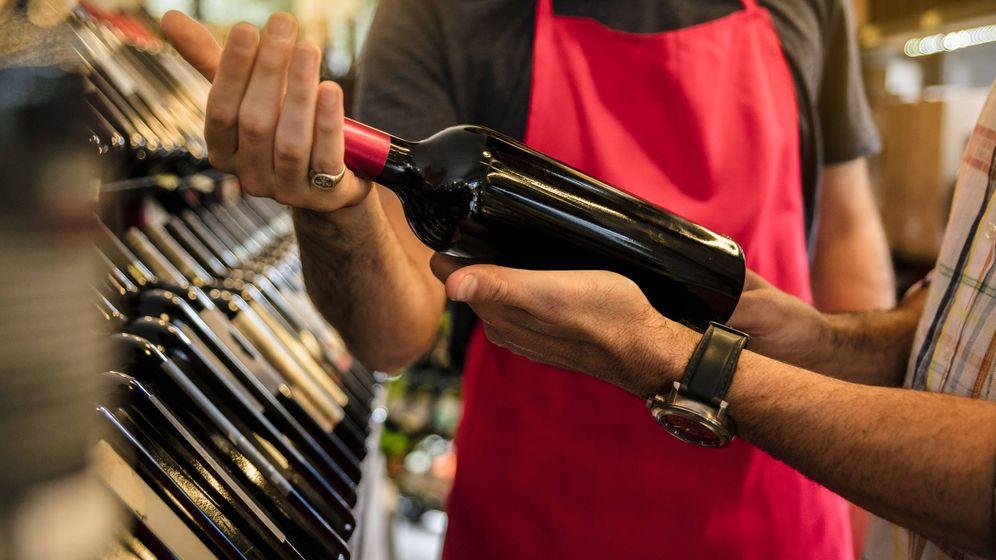 Foto: Un hombre ayudando a elegir un buen vino. (iStock)