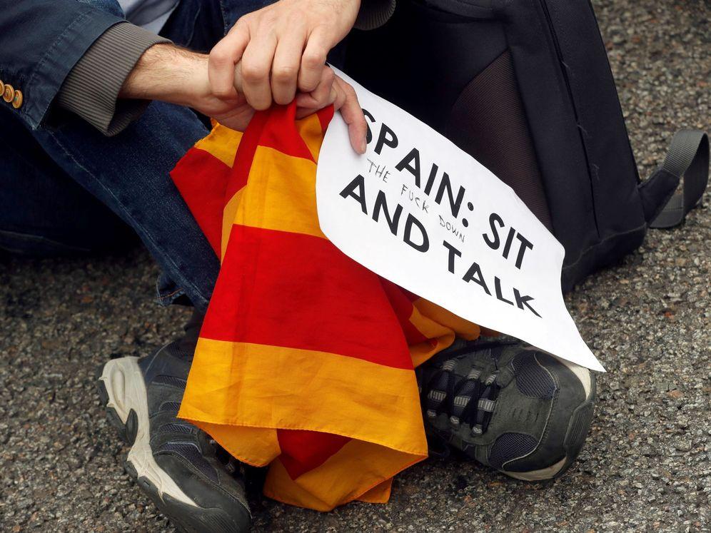 Foto: Un manifestante, con un cartel en el que pide que España se siente a dialogar. (EFE)