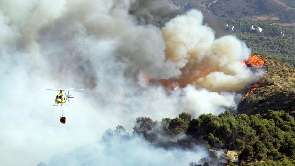 Foto: Un helicóptero, durante las labores de extinción del incendio forestal en Granada. (EFE)